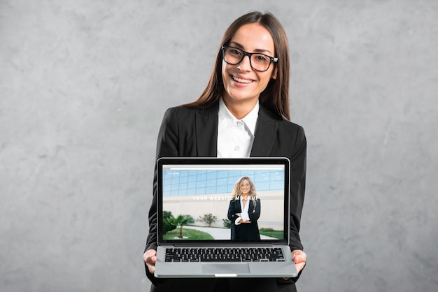 Woman presenting laptop mockup Free Psd