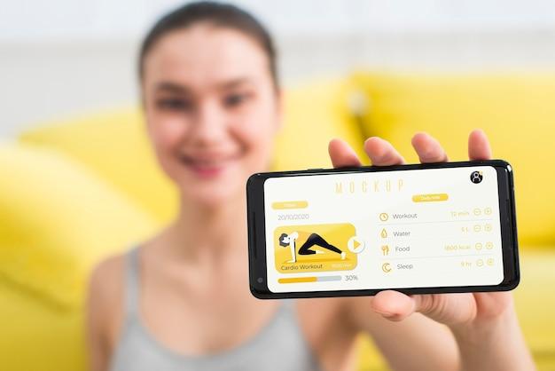 Женщина показывает фитнес-упражнения на мобильном телефоне Бесплатные Psd