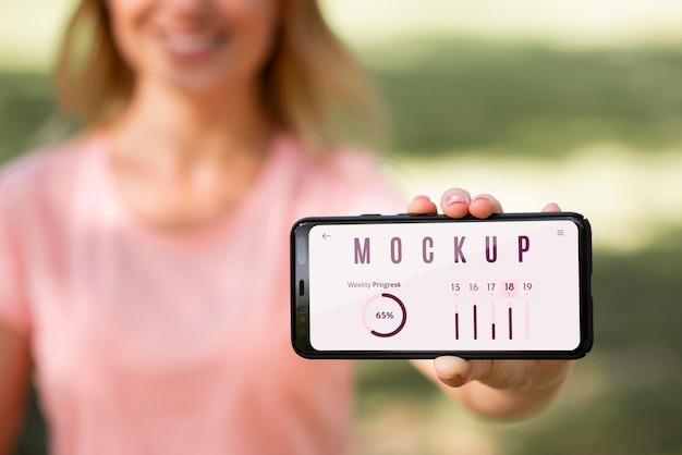 Женщина показывает телефон с макетным экраном на открытом воздухе Бесплатные Psd