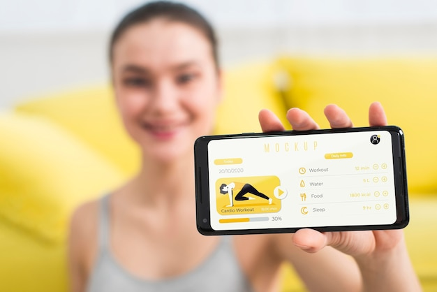 Woman showing a fitness exercise on mobile phone Free Psd