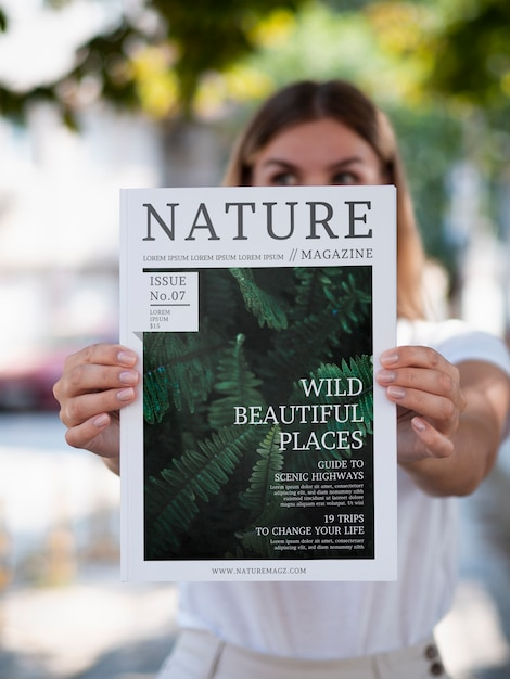 Woman showing a nature magazine mock up Free Psd