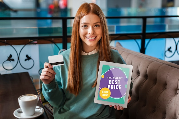 Woman smiling with a credit card and a tablet in her hands Free Psd