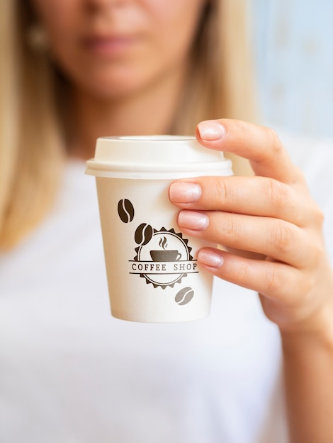 Woman wanting to drink from a coffee paper cup Free Psd