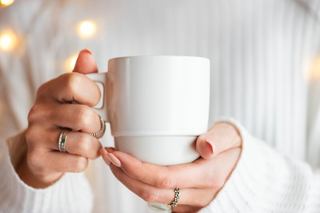 Woman in a white sweater with a white cup mockup Free Psd