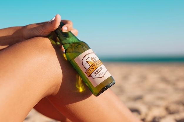 Woman with beer bottle mockup at the beach Free Psd