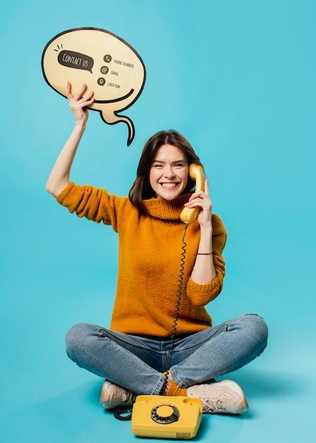 Donna con bolla di chat e vecchio telefono mock-up Psd Gratuite