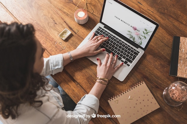 Woman working with laptop on wooden table Free Psd