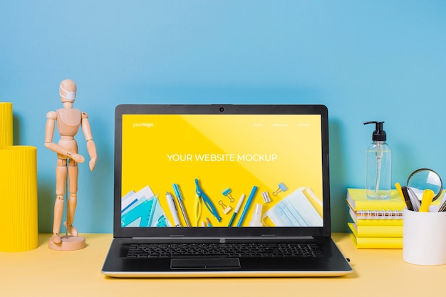 Manichino e laptop in legno con mock-up Psd Gratuite