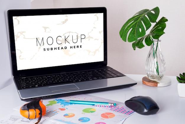 Рабочее место с ноутбуком, рисунком и листьями монстера Premium Psd