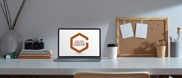Worktable with mockup laptop, stationery and camera Premium Psd