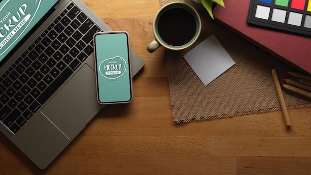 モックアップのスマートフォン、ラップトップ、コーヒーを備えた作業台 Premium Psd