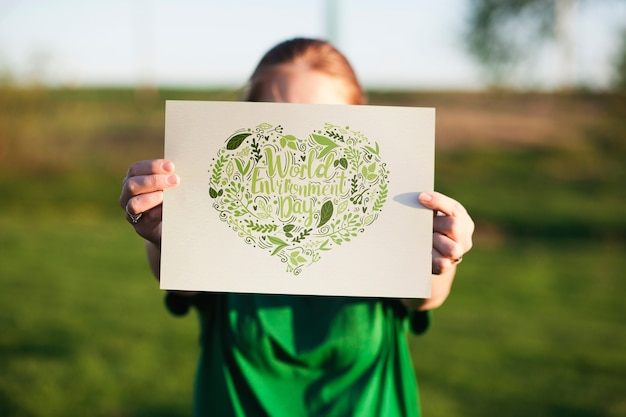 World environment day mockup with volunteer holding paper Free Psd