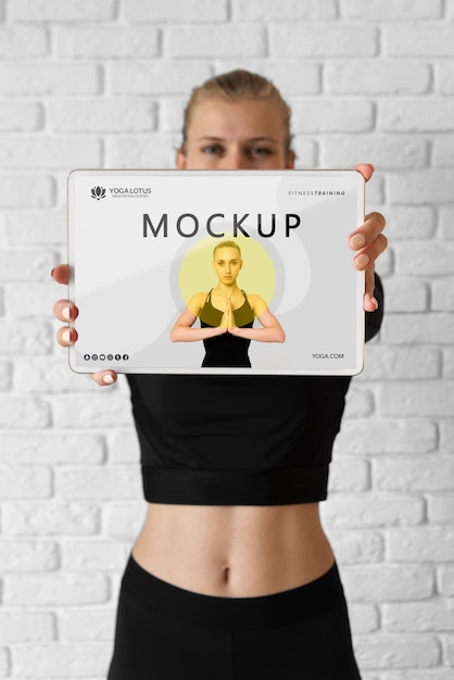 Инструктор по йоге держит макет планшета Premium Psd