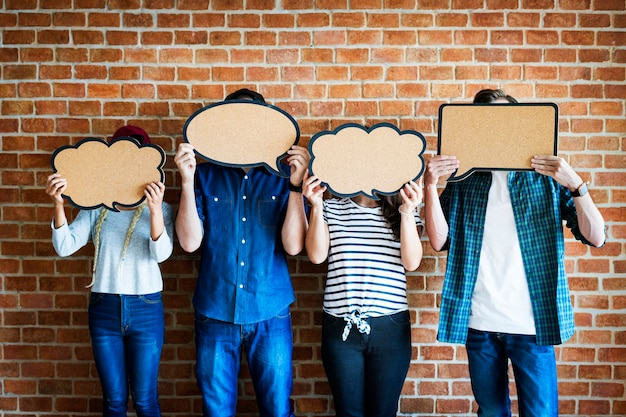 Young adults holding up copyspace placard thought bubbles Premium Psd