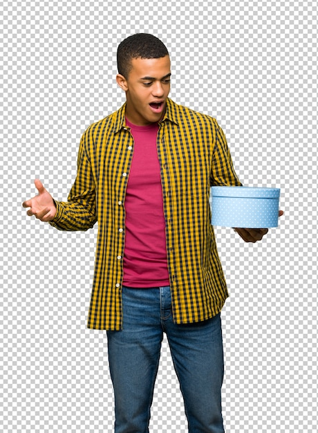 Young afro american man holding gift box in hands Premium Psd