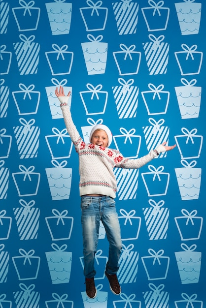 Young boy dressed christmas thematic sweater jumping Free Psd