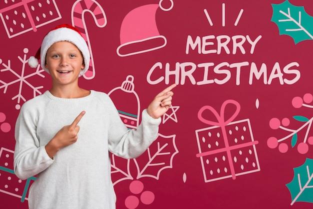 Молодой мальчик, указывая на сообщение на рождество Бесплатные Psd