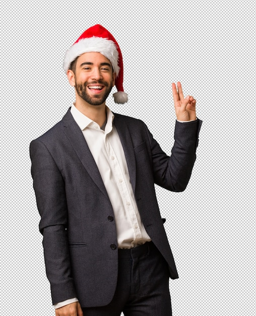 d2fd245bb0139 Young business man wearing santa hat doing a gesture of victory Premium Psd