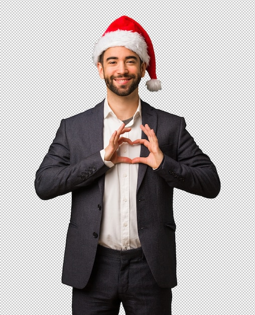 52d5a275c22dc Young business man wearing santa hat doing a heart shape with hands Premium  Psd