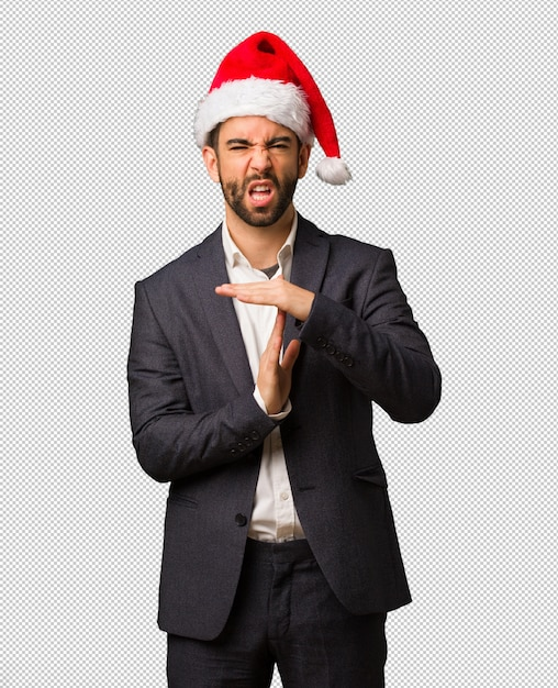 Young business man wearing santa hat doing a timeout gesture Premium Psd