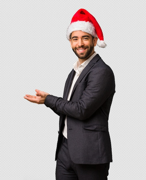 5bf8741775c8a Young business man wearing santa hat holding something with hands Premium  Psd