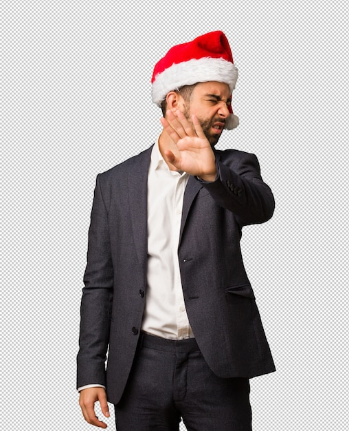 Young business man wearing santa hat putting hand in front Premium Psd