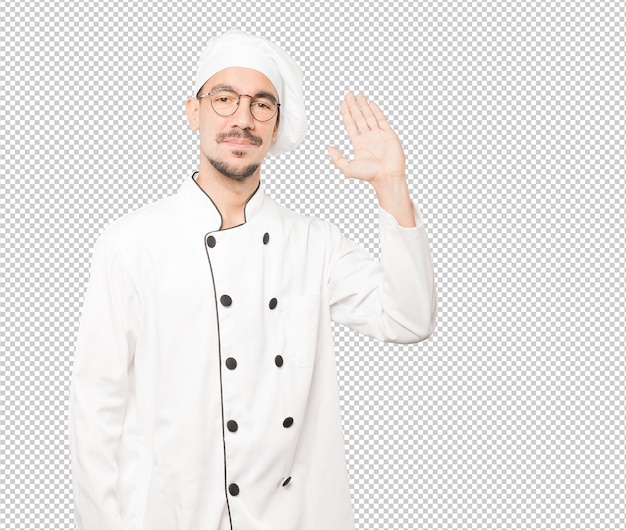 Young chef waving with his hand Premium Psd