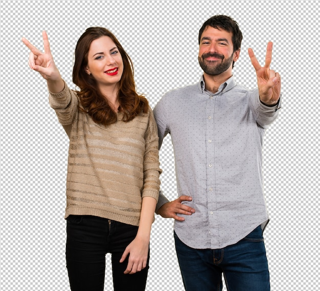 Young couple making victory gesture Premium Psd