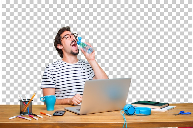 Young crazy graphic designer on a desk with a laptop and water bottle Premium Psd