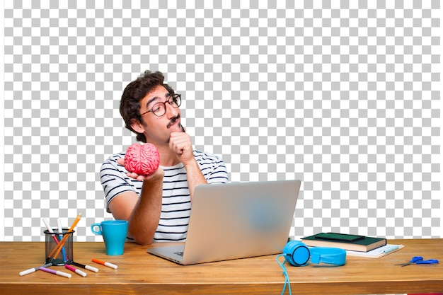 Young crazy graphic designer on a desk with a laptop and with a brain model Premium Psd