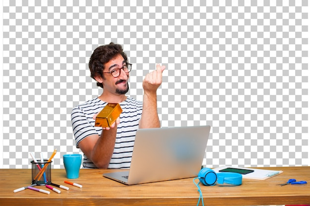 Young crazy graphic designer on a desk with a laptop and with a gold ingot Premium Psd