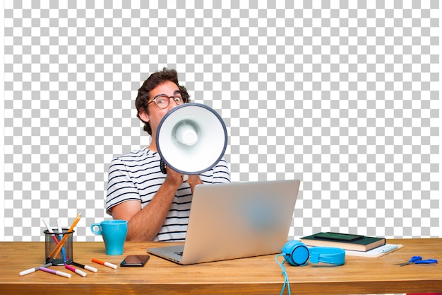 Young crazy graphic designer on a desk with a laptop and with a megaphone Premium Psd