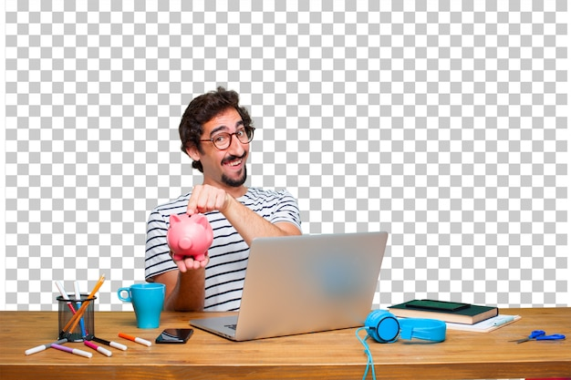 Young crazy graphic designer on a desk with a laptop and with a piggy bank Premium Psd