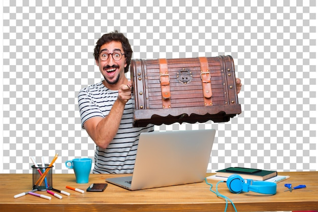 Young crazy graphic designer on a desk with a laptop and with a pirate chest Premium Psd