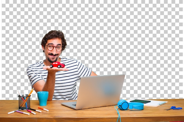 Young crazy graphic designer on a desk with a laptop and with a red car model Premium Psd