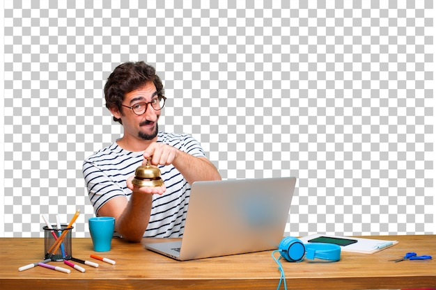 Young crazy graphic designer on a desk with a laptop and with a ring bell Premium Psd