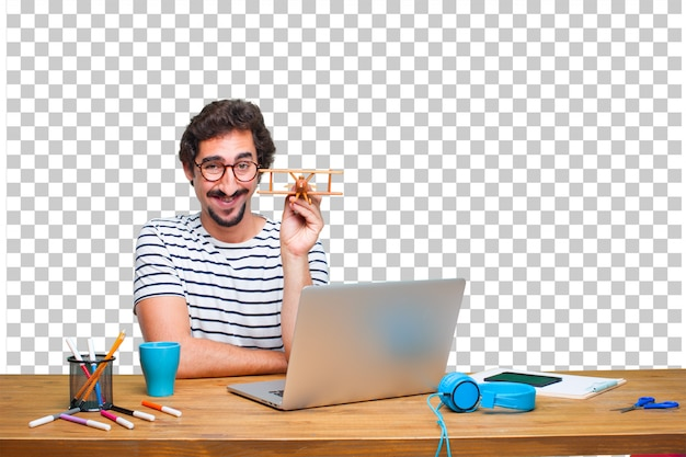 Young crazy graphic designer on a desk with a laptop and with a wooden plane Premium Psd