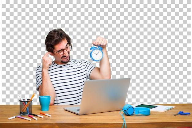 ノートパソコンと目覚まし時計を机の上の若いクレイジーグラフィックデザイナー Premium Psd