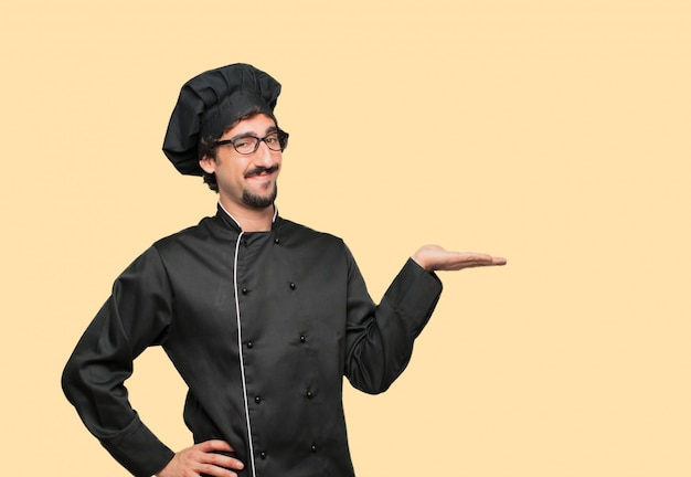 Young crazy man as a chef smiling with a satisfied expression showing an object or concept Premium Psd