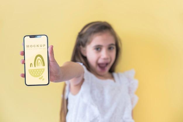 Ragazza giovane azienda telefono con mock-up Psd Gratuite