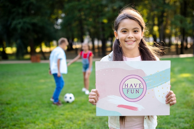 Young girl in park holding sign with positive message Free Psd