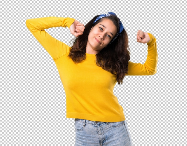 Young girl with yellow sweater and blue bandana on her head enjoy dancing Premium Psd