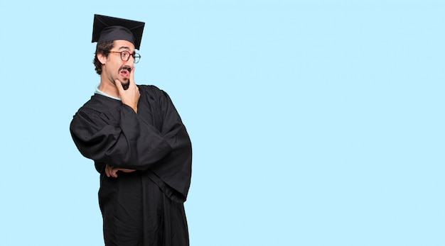 Young graduated man with a confused and thoughtful look, looking sideways Premium Psd
