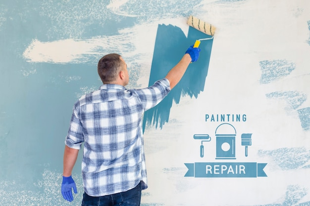 Young handyman painting the wall in blue Premium Psd