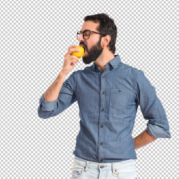 Young hipster man eating apple over white background Premium Psd