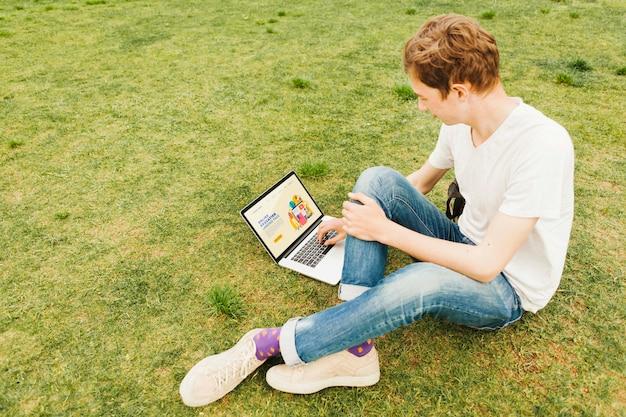야외에서 노트북에서 일하는 젊은 남성 무료 PSD 파일