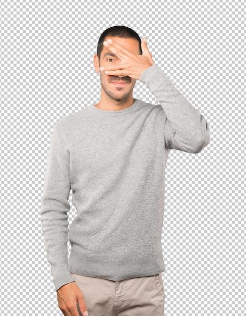 彼の手で彼の目を覆っている若い男 Premium Psd