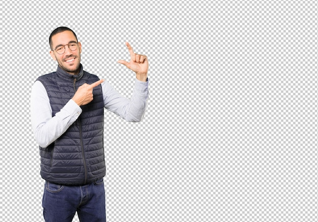 Young man doing a gesture of small size with his hand Premium Psd