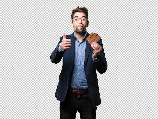 Young man eating a chocolate bar Premium Psd