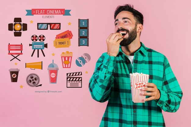 Young man eating popcorn next to cinema elements Free Psd
